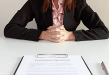 An image of a woman sitting at a table with an employment contract on the table.