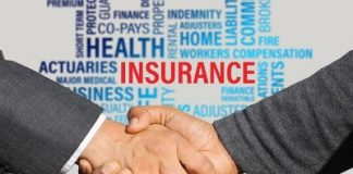 Two people shaking hands with Insurance signs in the background.